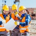 Three workers examining building plans at construction site