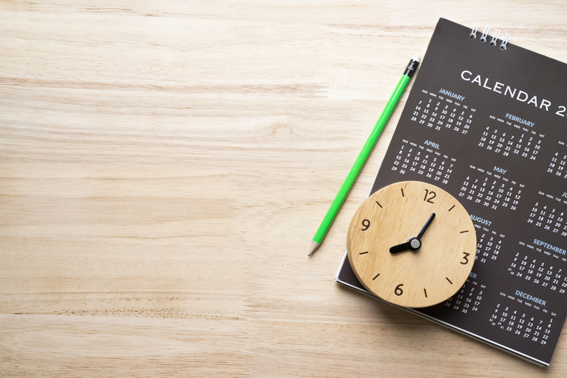 close up of calendar, pencil and clock on the table, planning for business meeting or travel planning concept